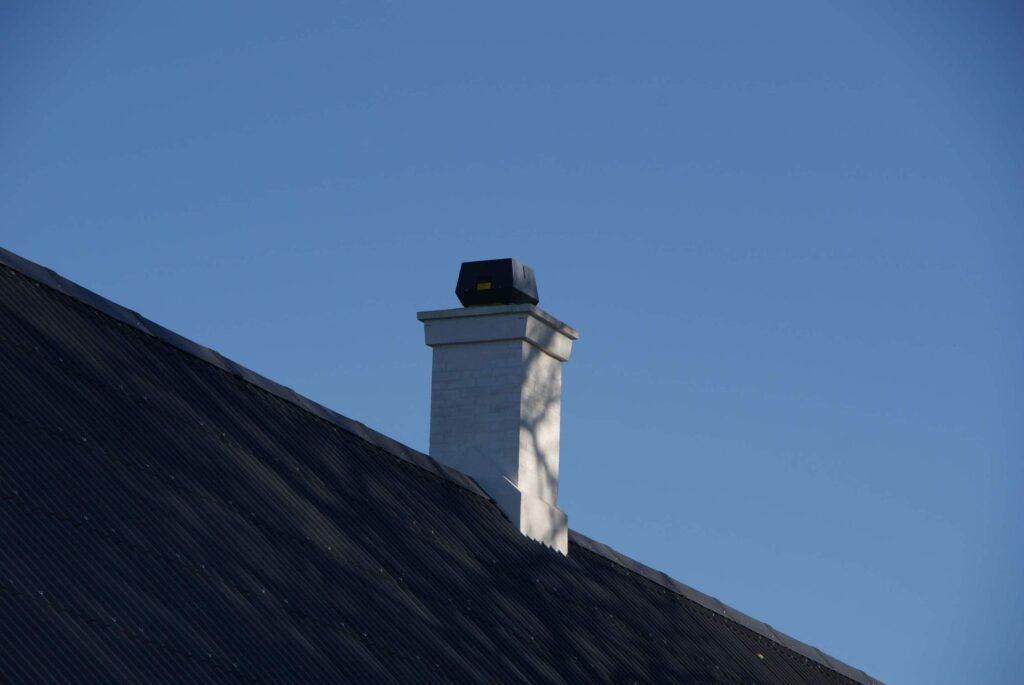 Røgsuger monteret på muret skorsten.